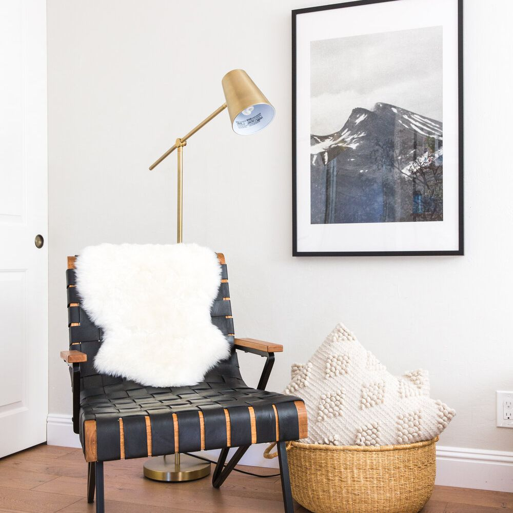 A bedroom corner decorated with a woven basket filled with pillows