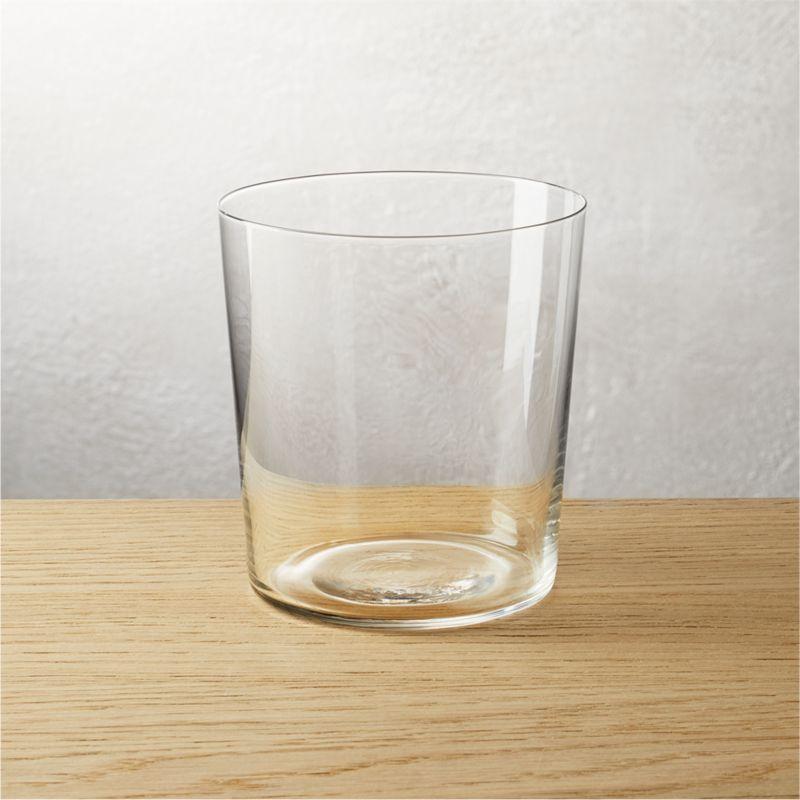 A rocks glass on a wood surface.
