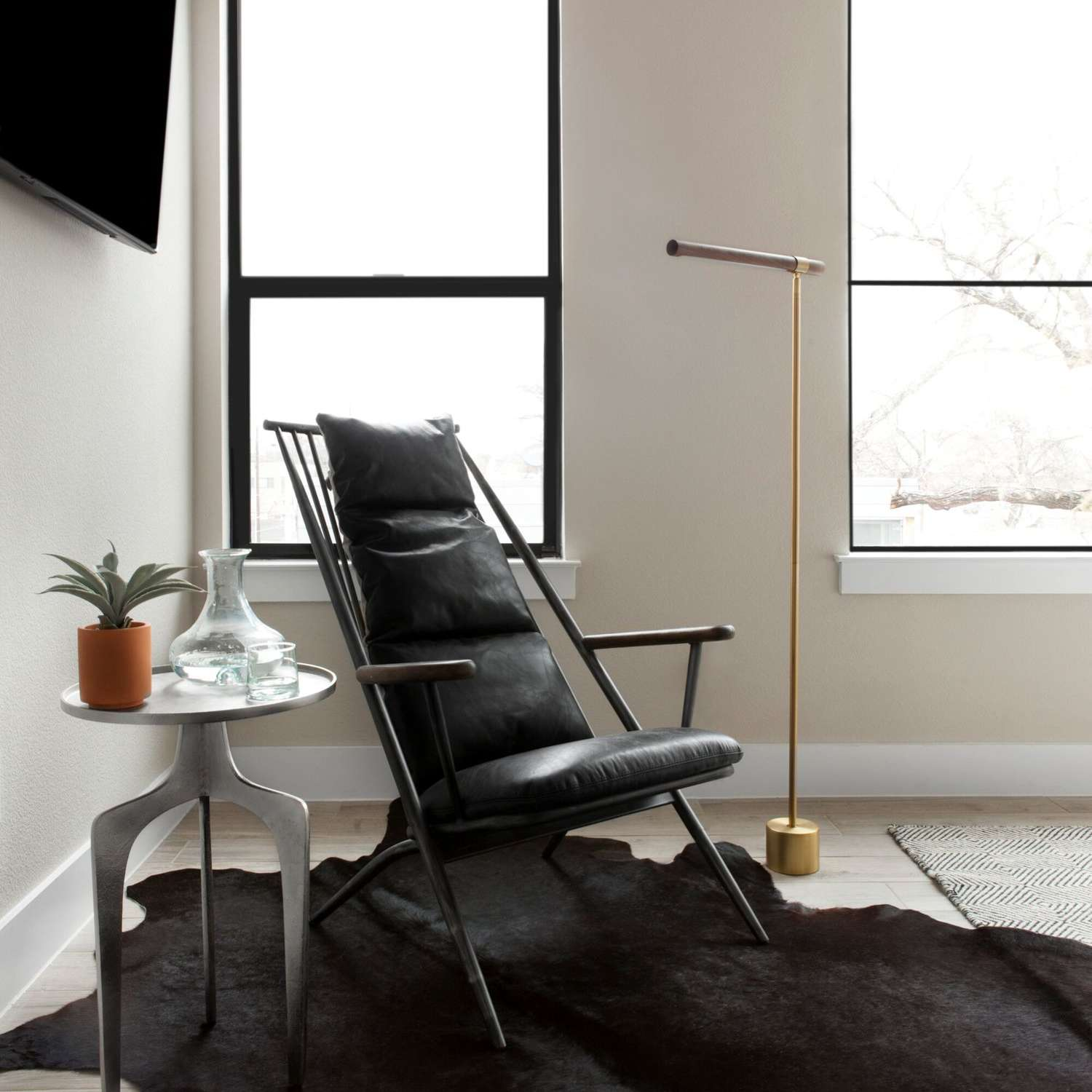 A corner decorated with sleek industrial furniture and a black cow hide rug