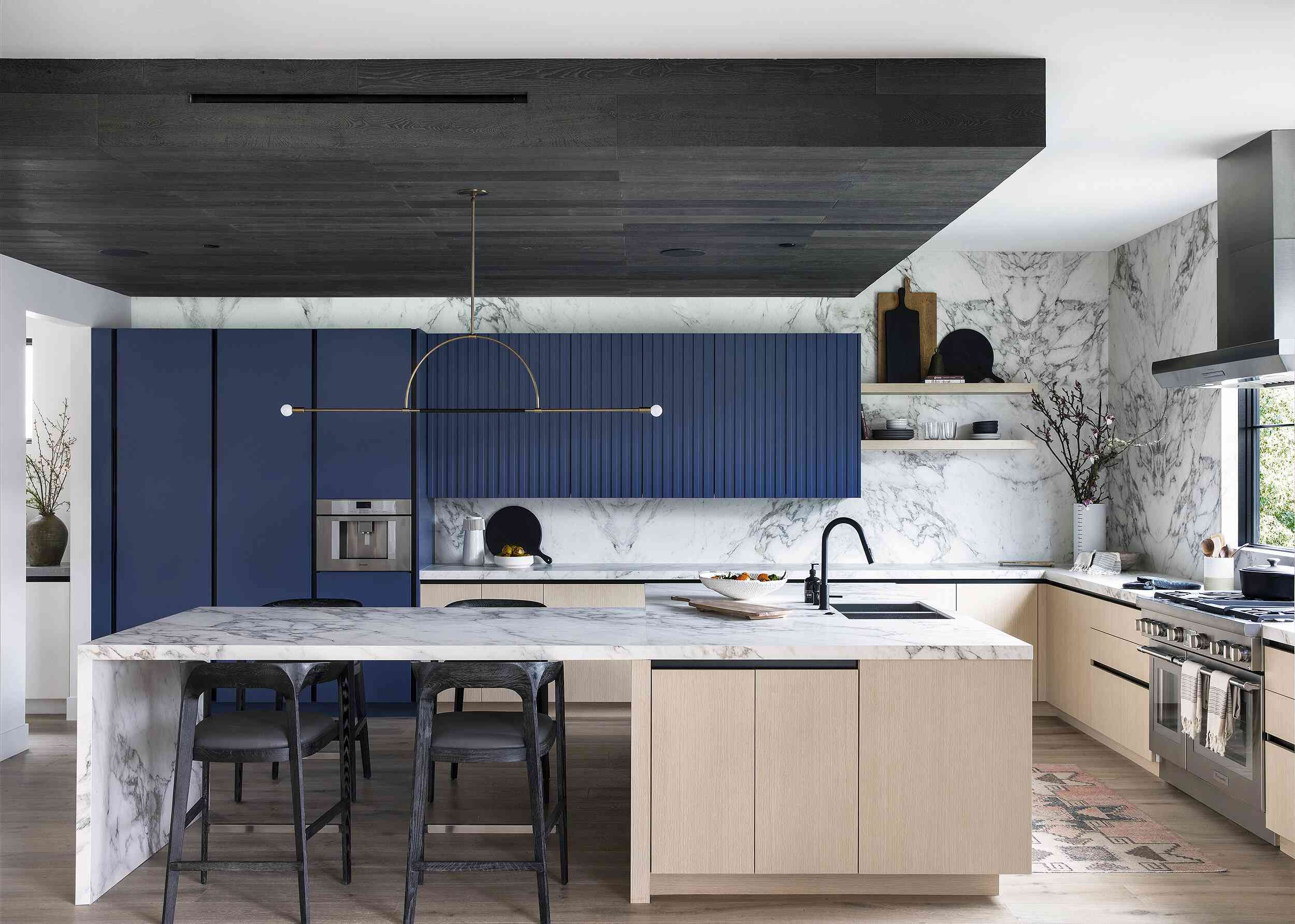 A kitchen with a striking marble backsplash that runs from ceiling to countertop