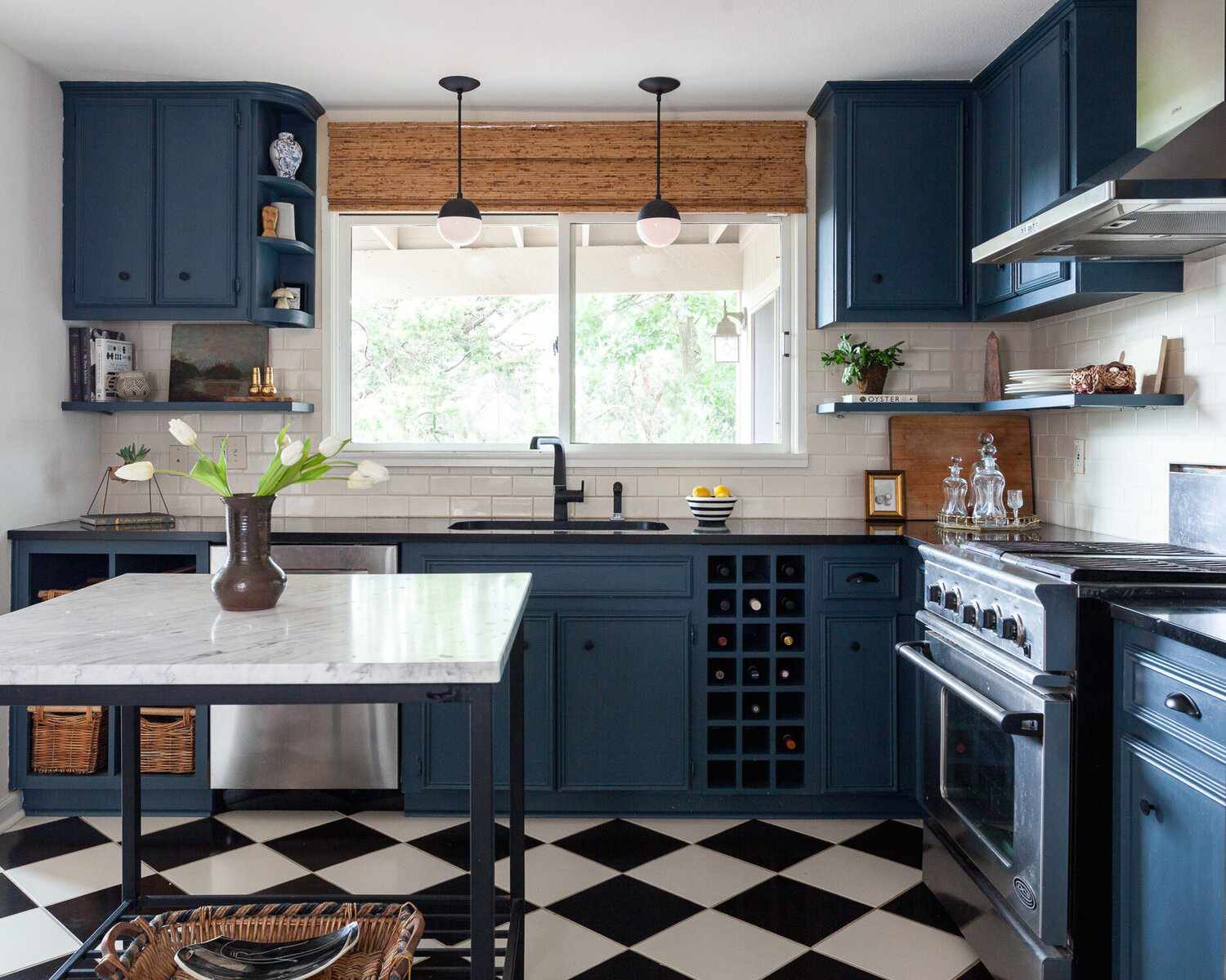 A kitchen with blue cabinets and black-and-white tiled floors
