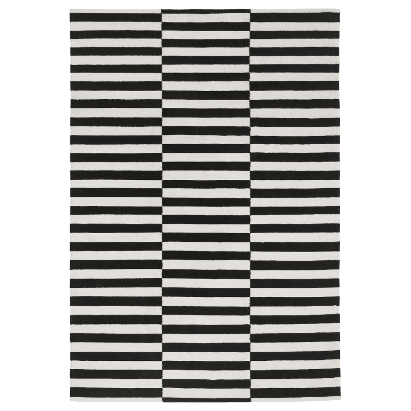 A black and white striped flatweave rug.