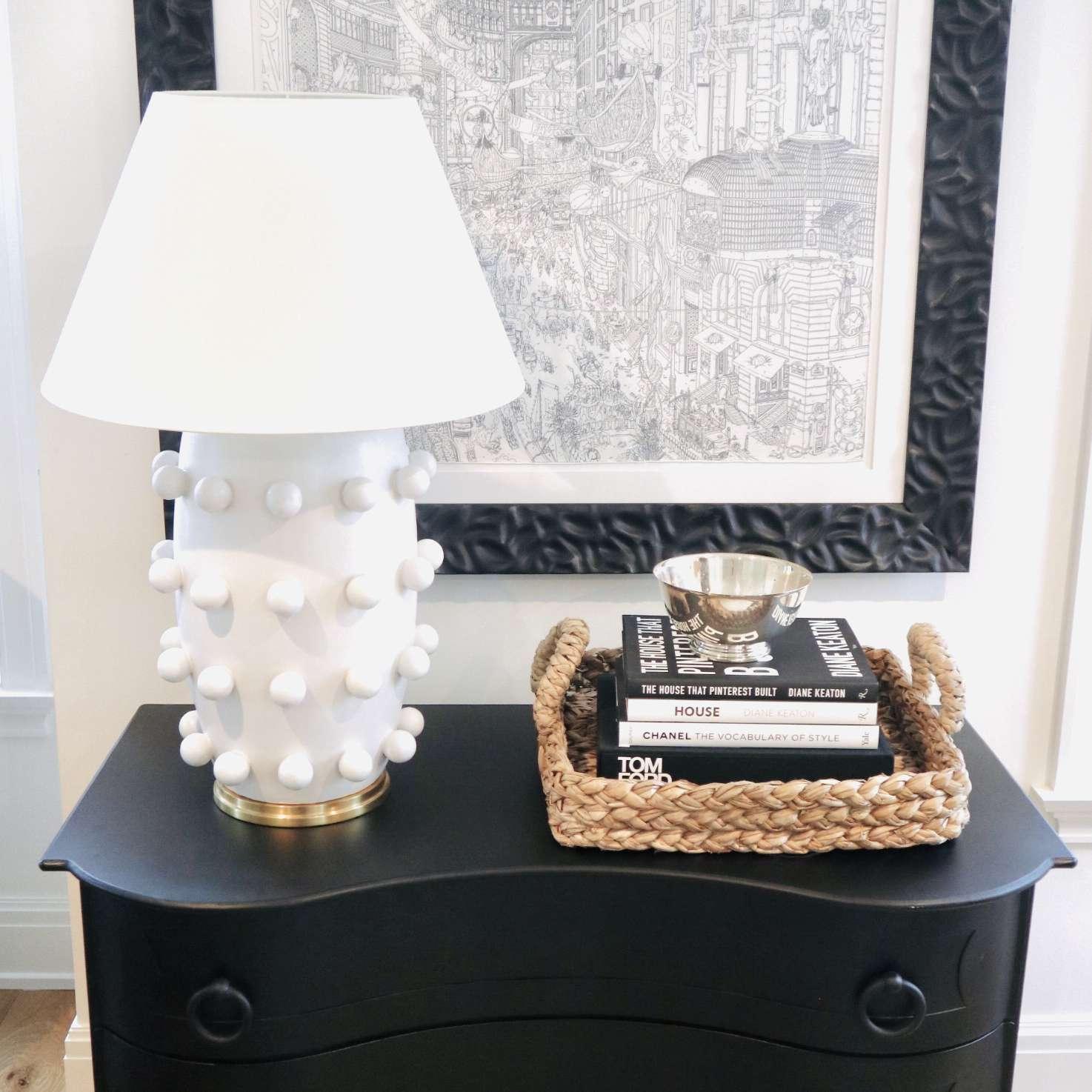 Black dresser with white lamp.