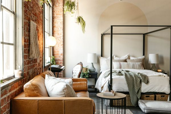 arizona loft makeover - leather couch and four-poster bed in open studio space
