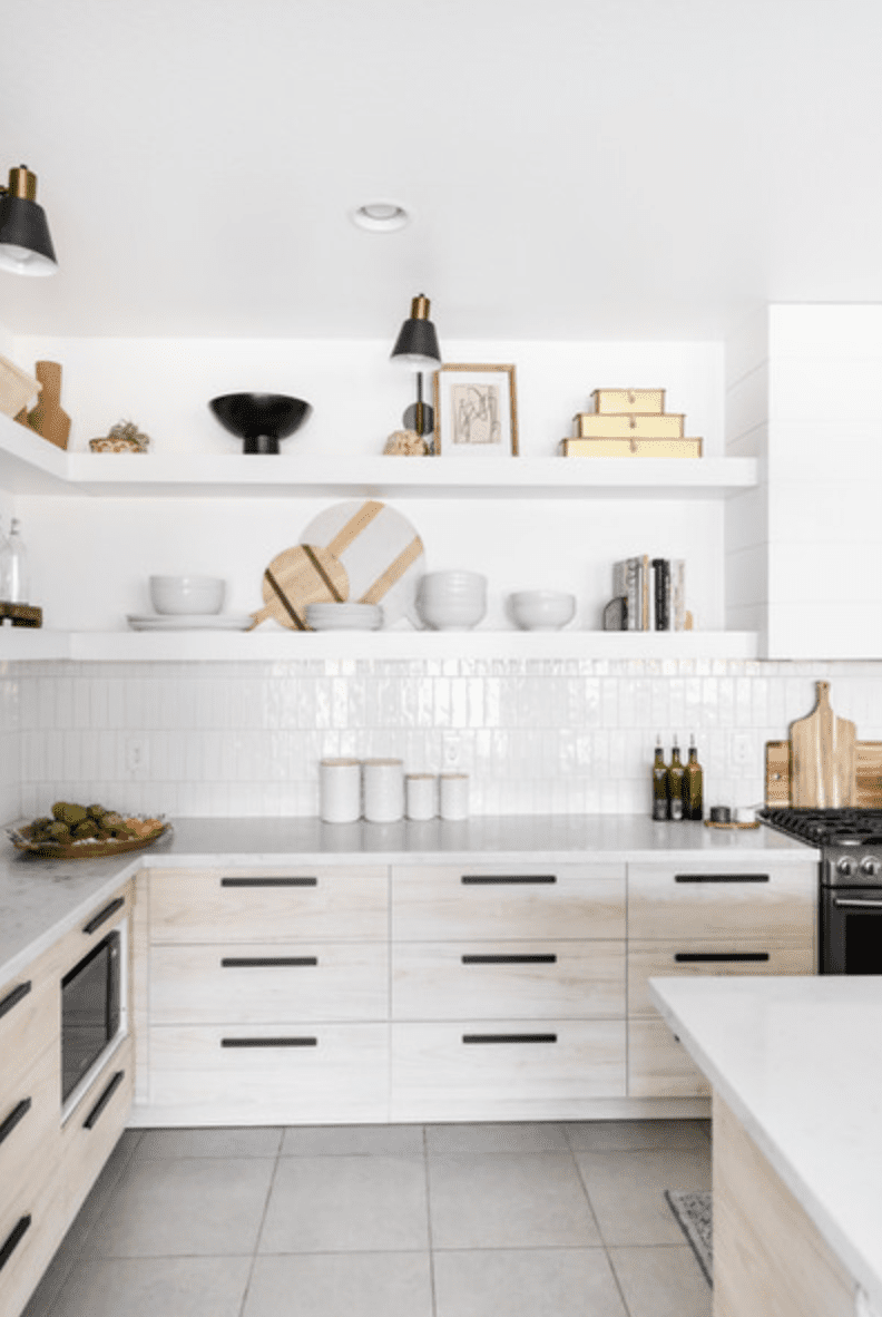 A kitchen lined with white rectangular tiles, which have been turned vertically