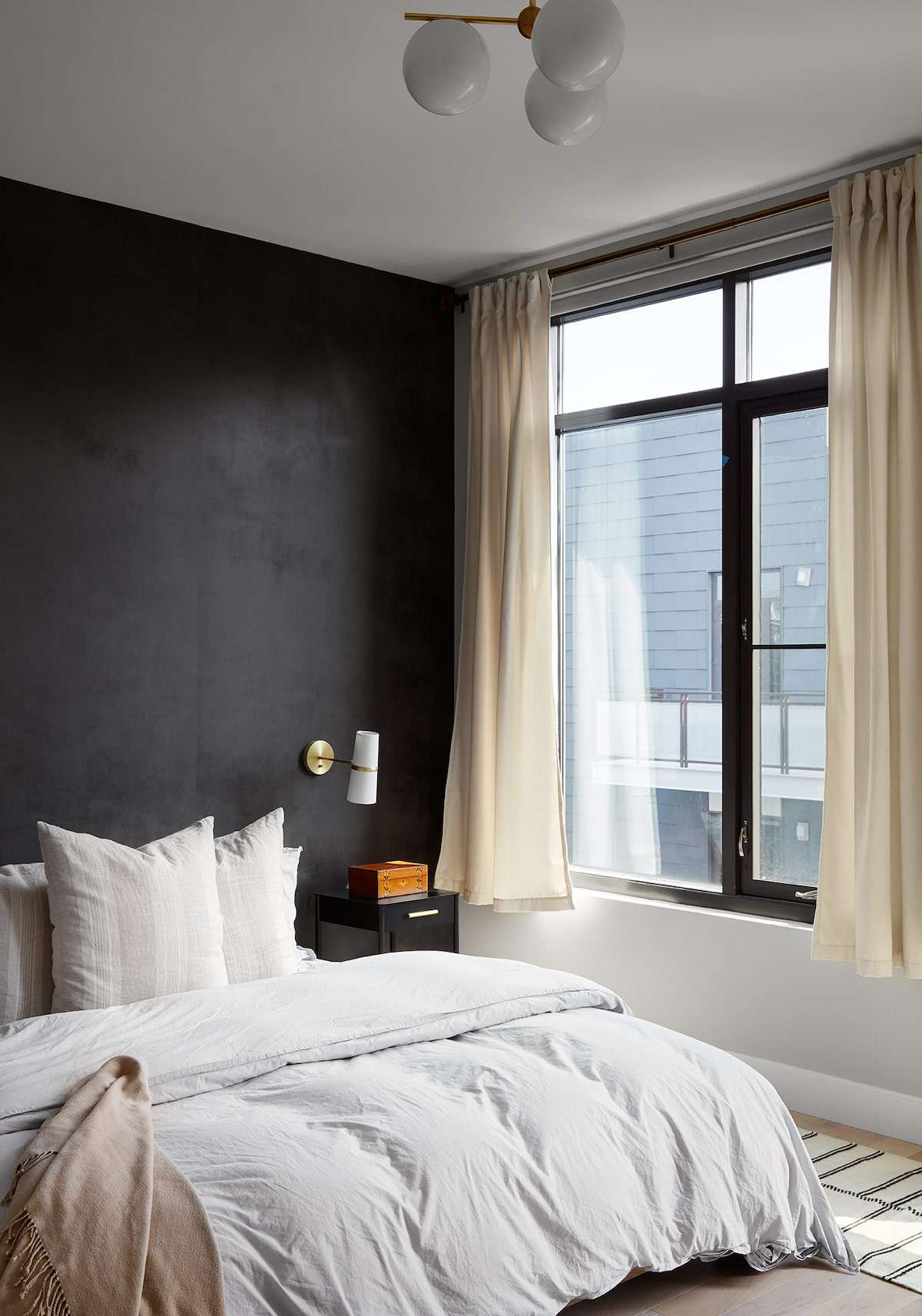 A dark bedroom with short curtains