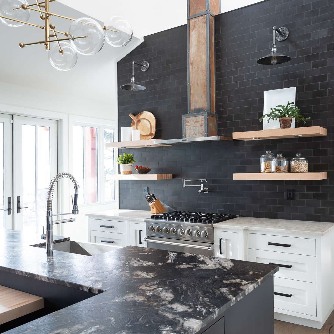 A kitchen lined with black tiles, black cabinets, and black marble countertops