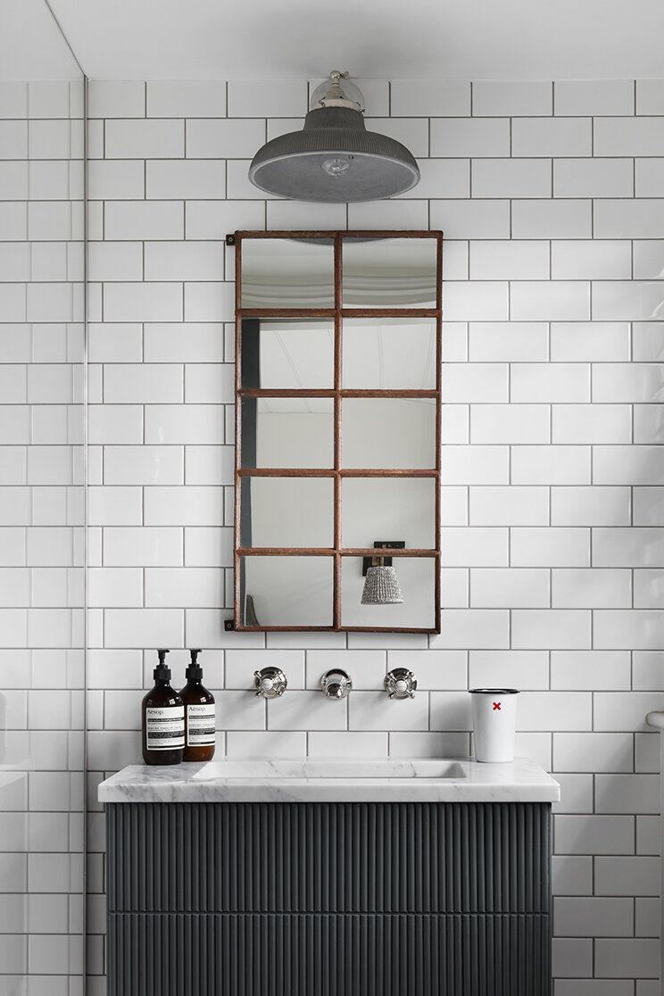 A bathroom lined with white tiles and decorated with a bold mirror