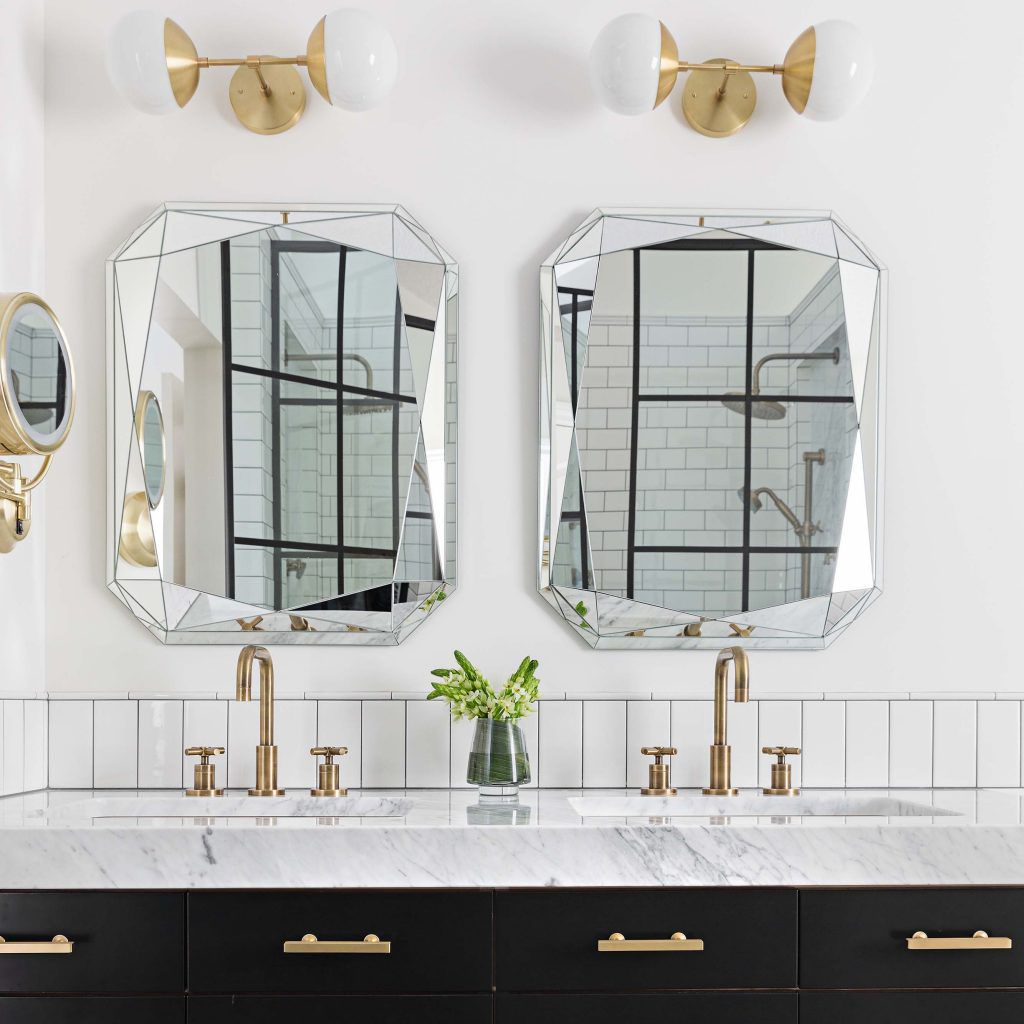 Two silver mirrors above a marble bathroom sink.
