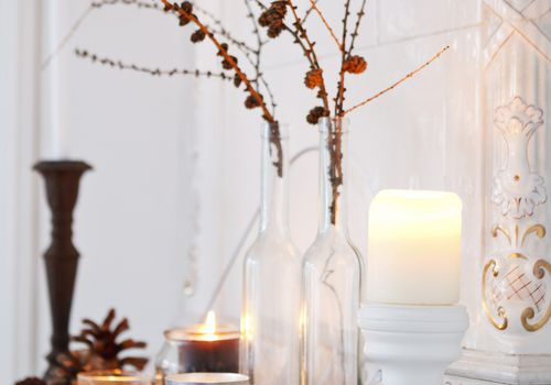 Candles and pinecone décor on a mantle