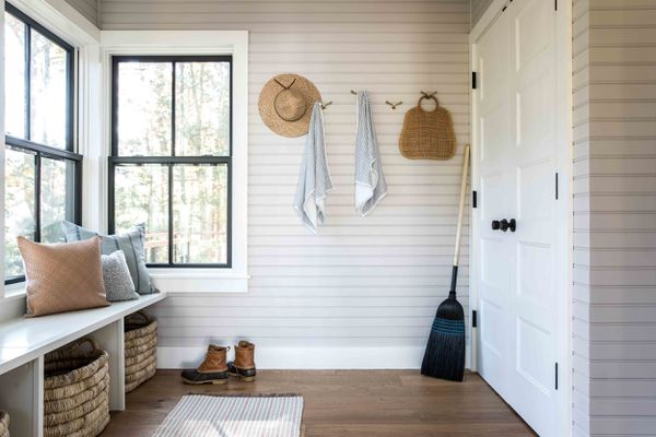 A large mudroom with a closet, several hooks, and a few baskets
