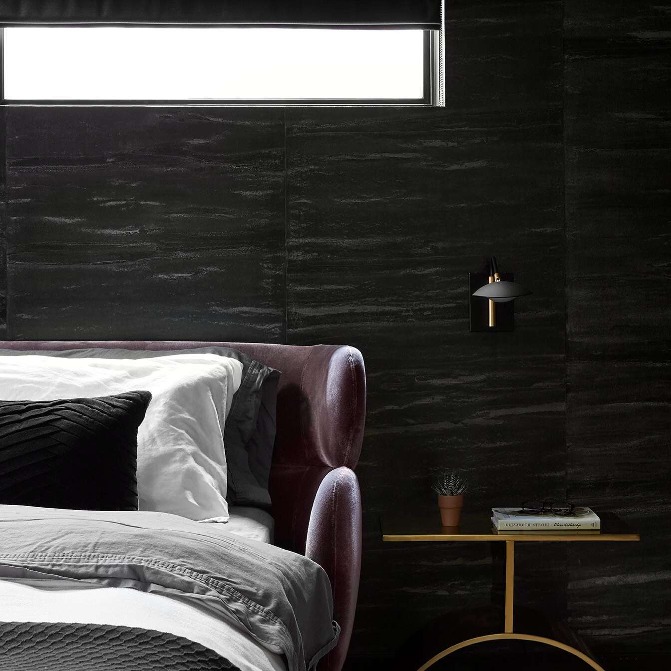 Sleek and chic black and gray bedroom with stone-look wall texture