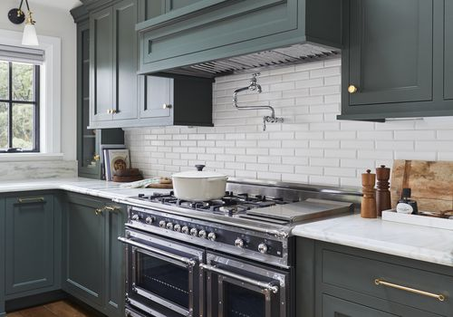 kitchen with sage green cabinets and large stove