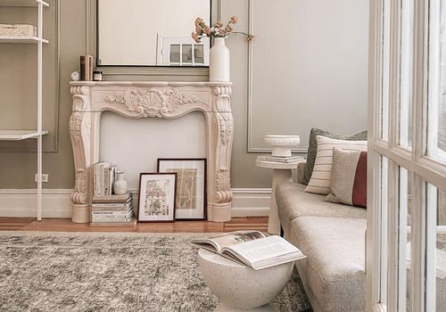 Parisian style living room with ornate mantle and neutral details.