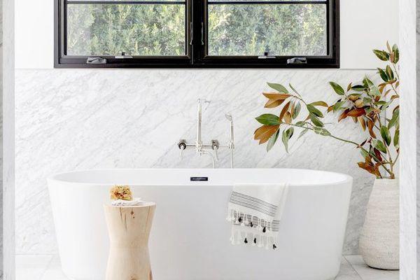 Soaking tub with marble backsplash and black-trimmed window
