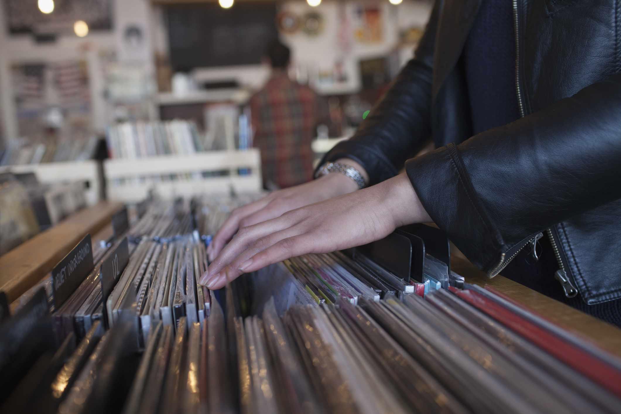 Hands rifle through vinyl records