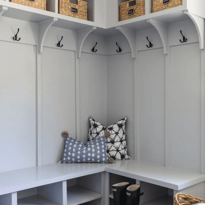 A light gray mudroom lined with shelves and hangers