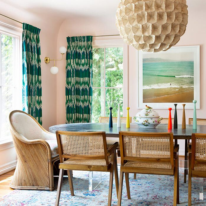 Dining room with rattan chairs and light pink walls.