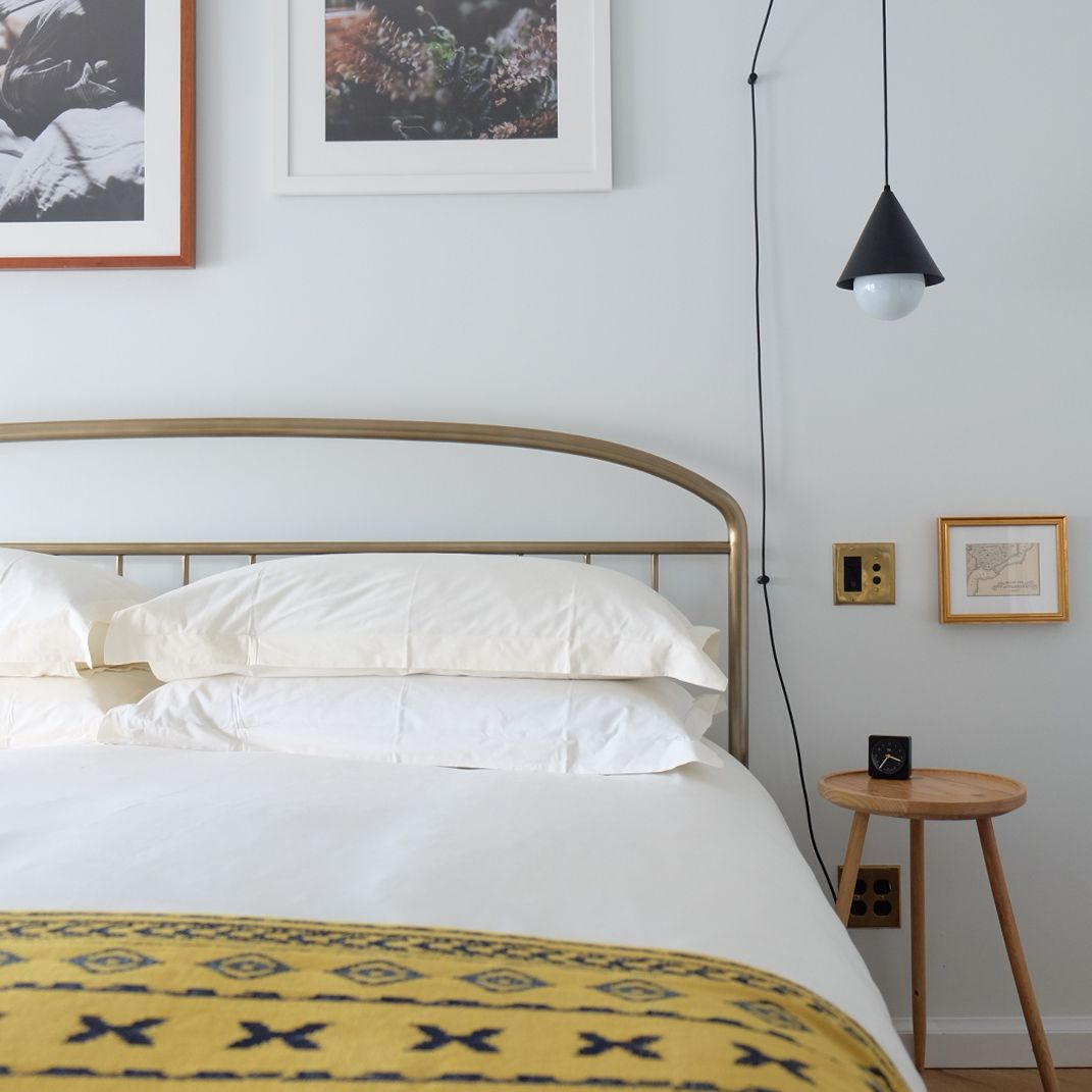 Simple scandi bedroom with yellow patterned throw