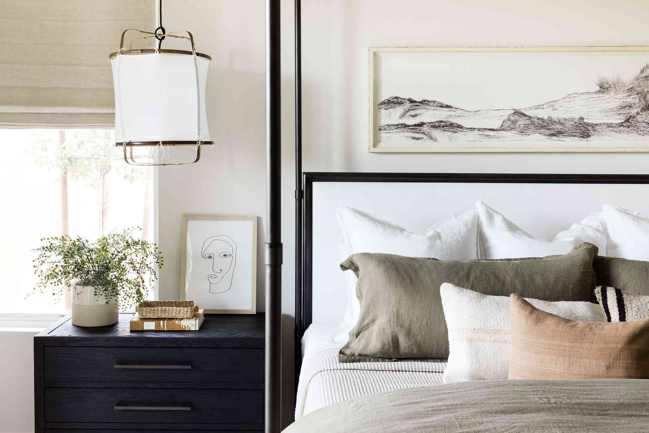 A neutral-filled bedroom with a black canopy bed