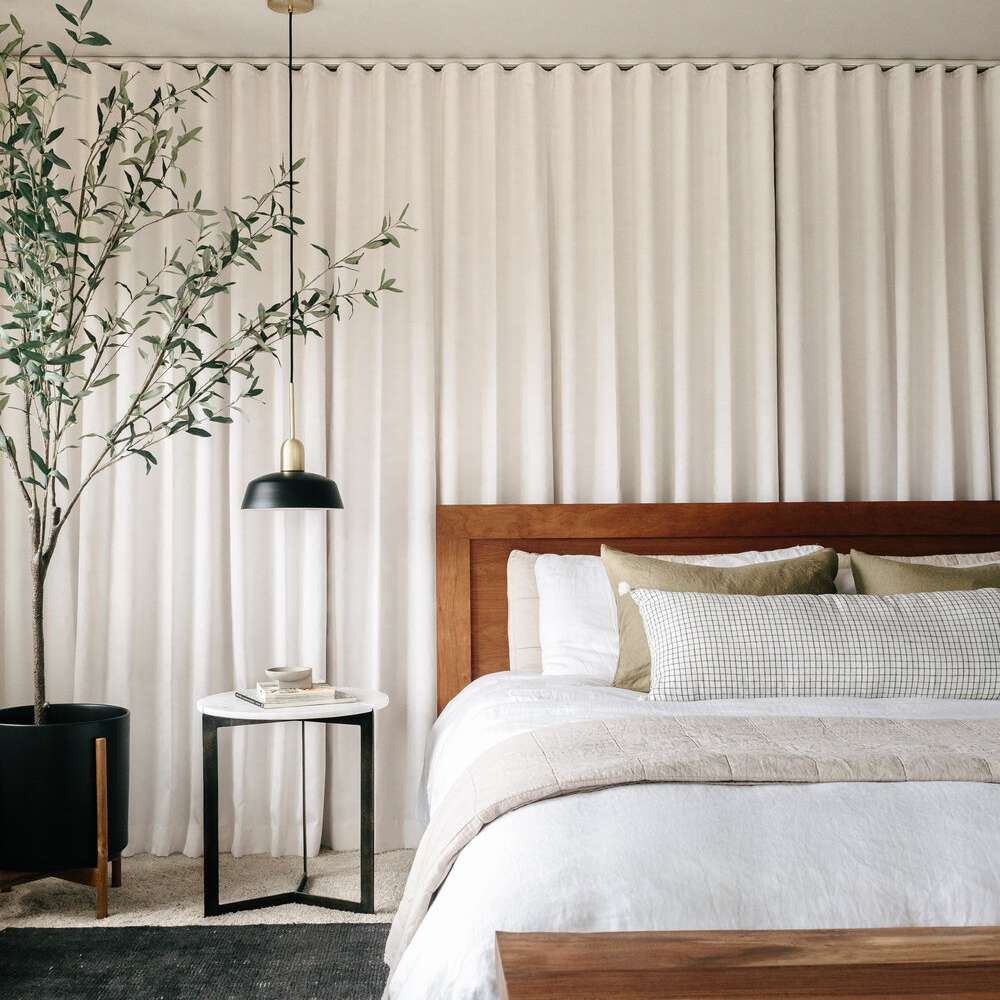 A bedroom lined with ivory drapes