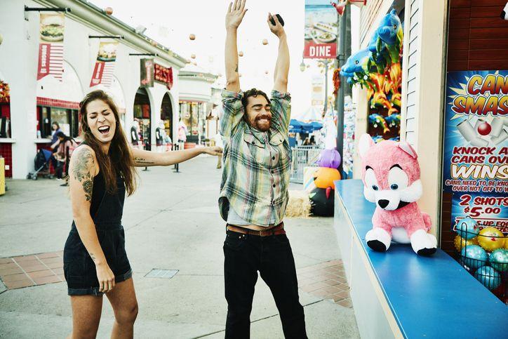 Man celebrating after winning carnival game at amusement park