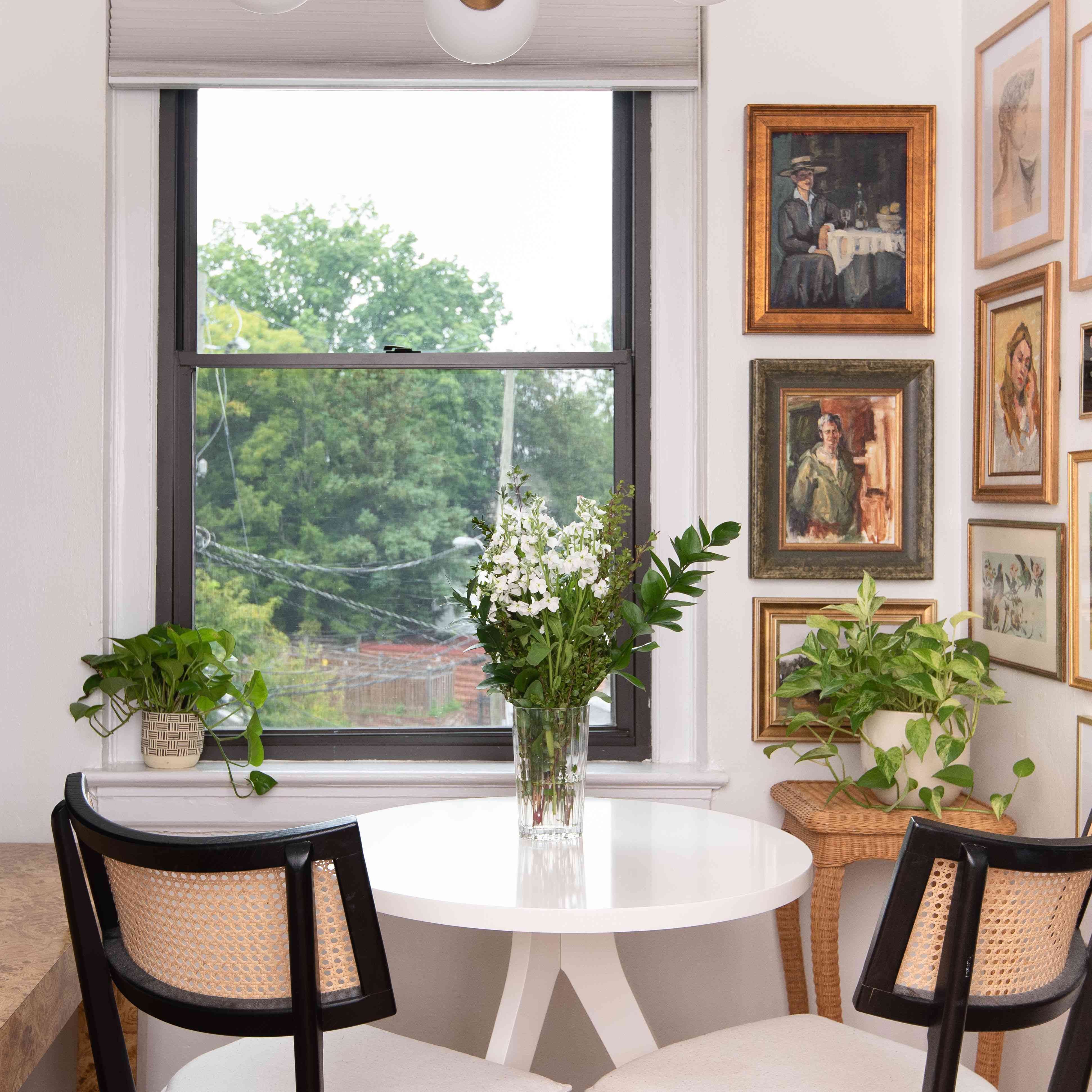 Dining nook with corner full of traditional antique art.