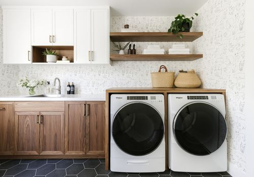 A laundry room with wooden cabinets and cat wallpaper