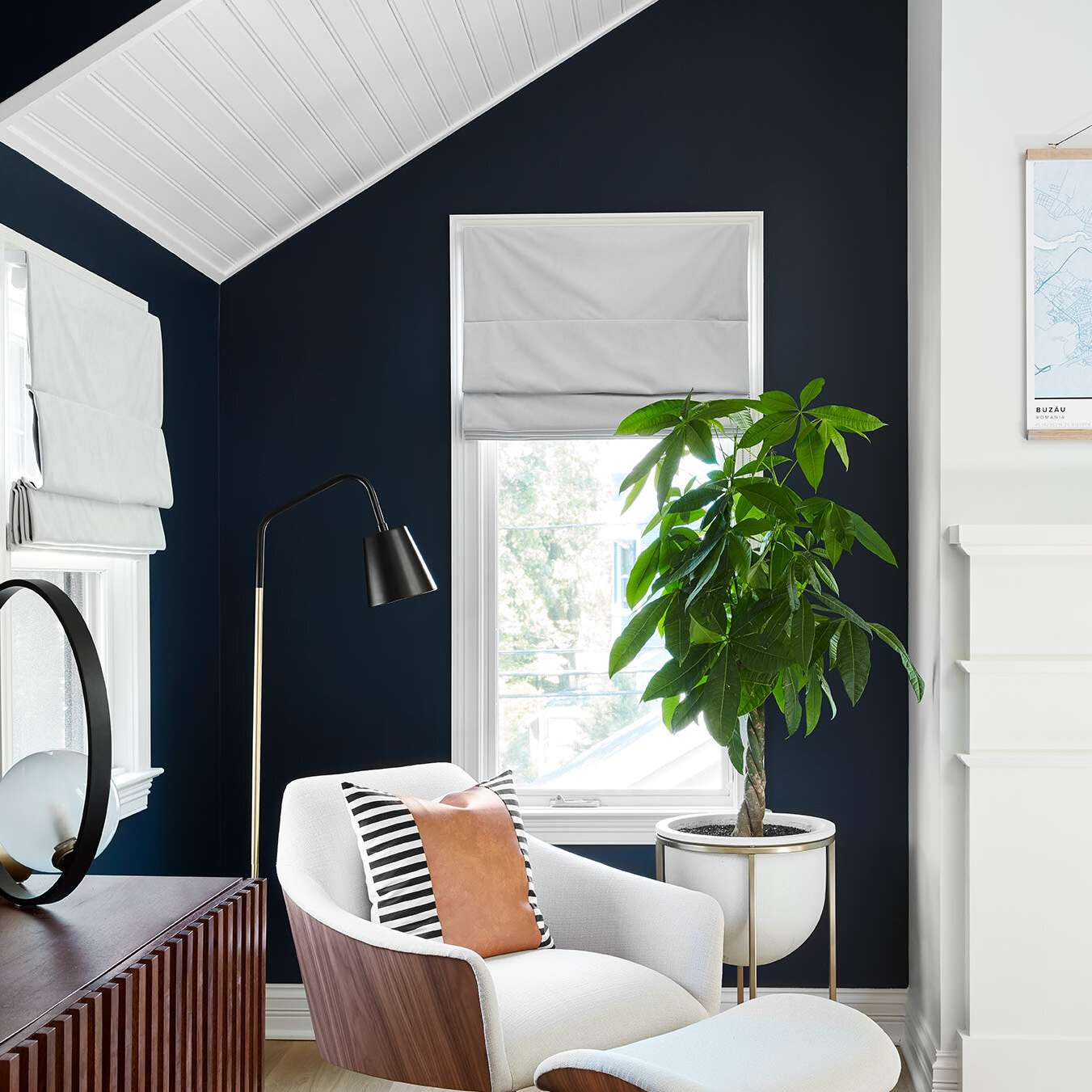 A bedroom corner with indigo walls and a white ceiling
