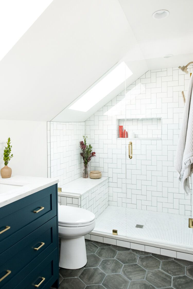 A small bathroom with a slanted ceiling, and a shower with a built-in seat tucked under that ceiling