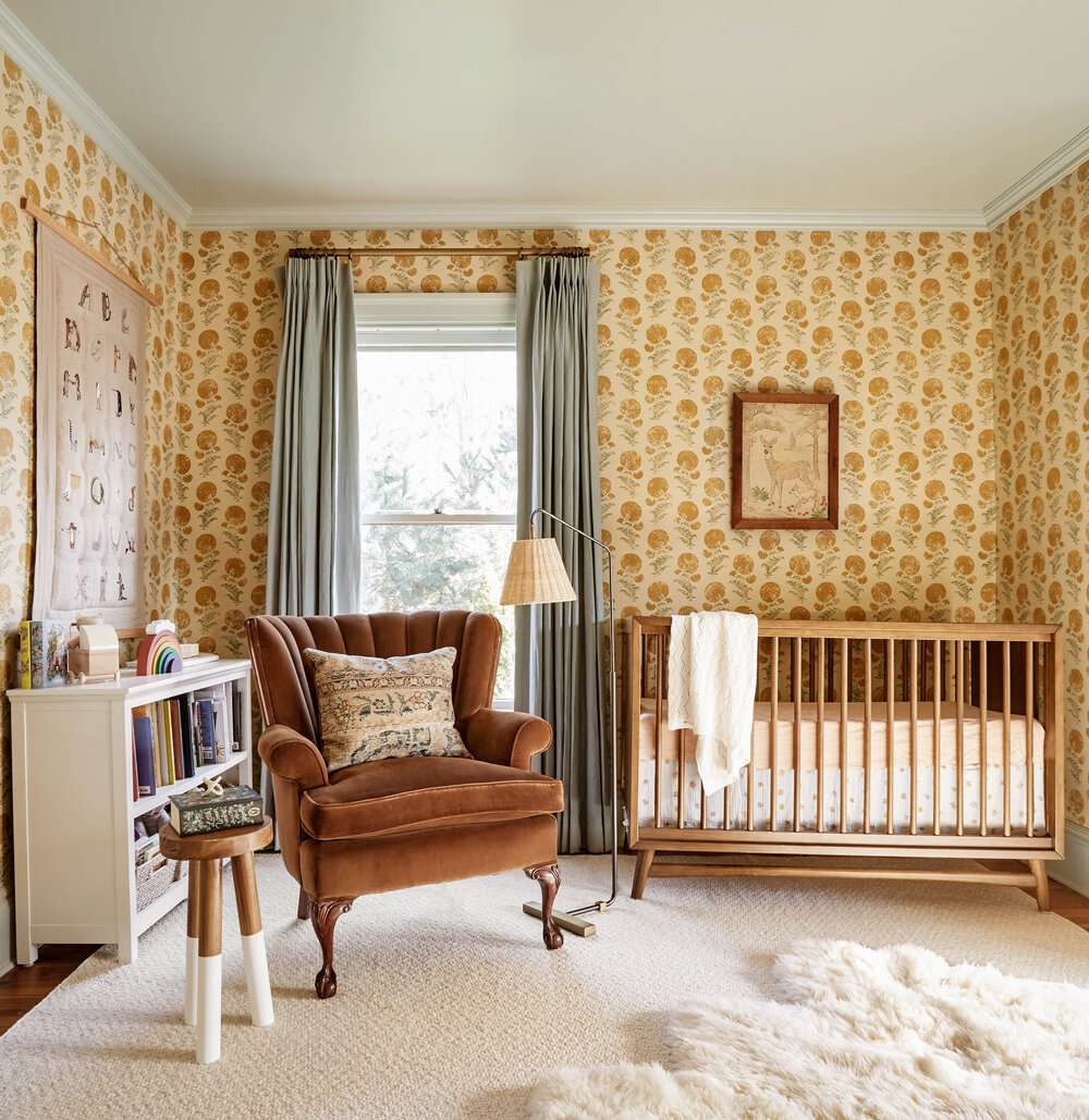nursery with vintage style chair, crib, and wallpaper