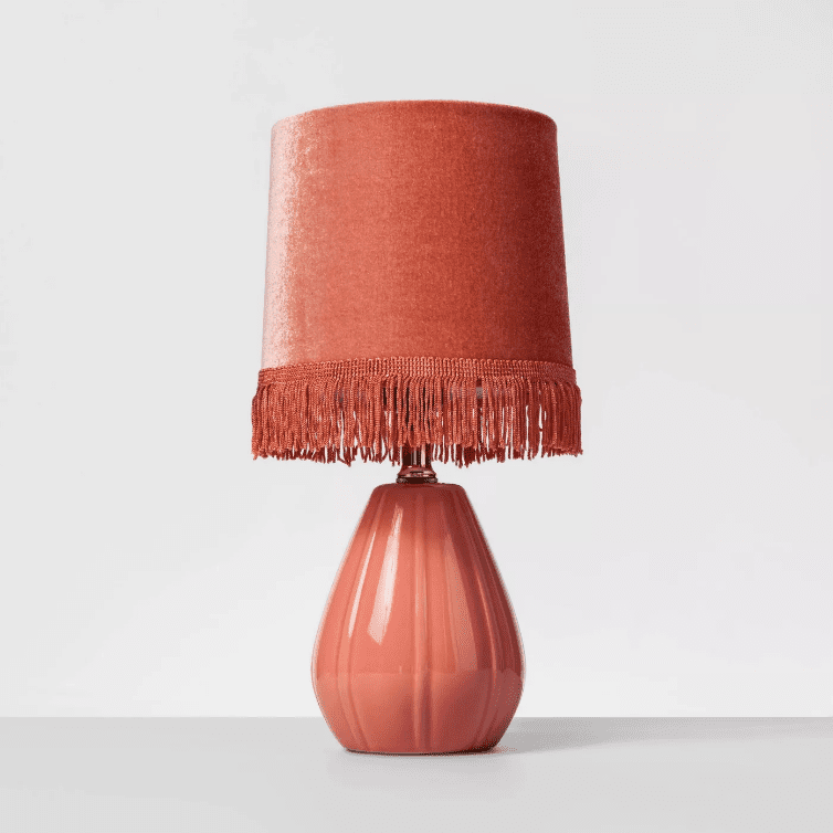 A pink ceramic table lamp with a fringed velvet shade.