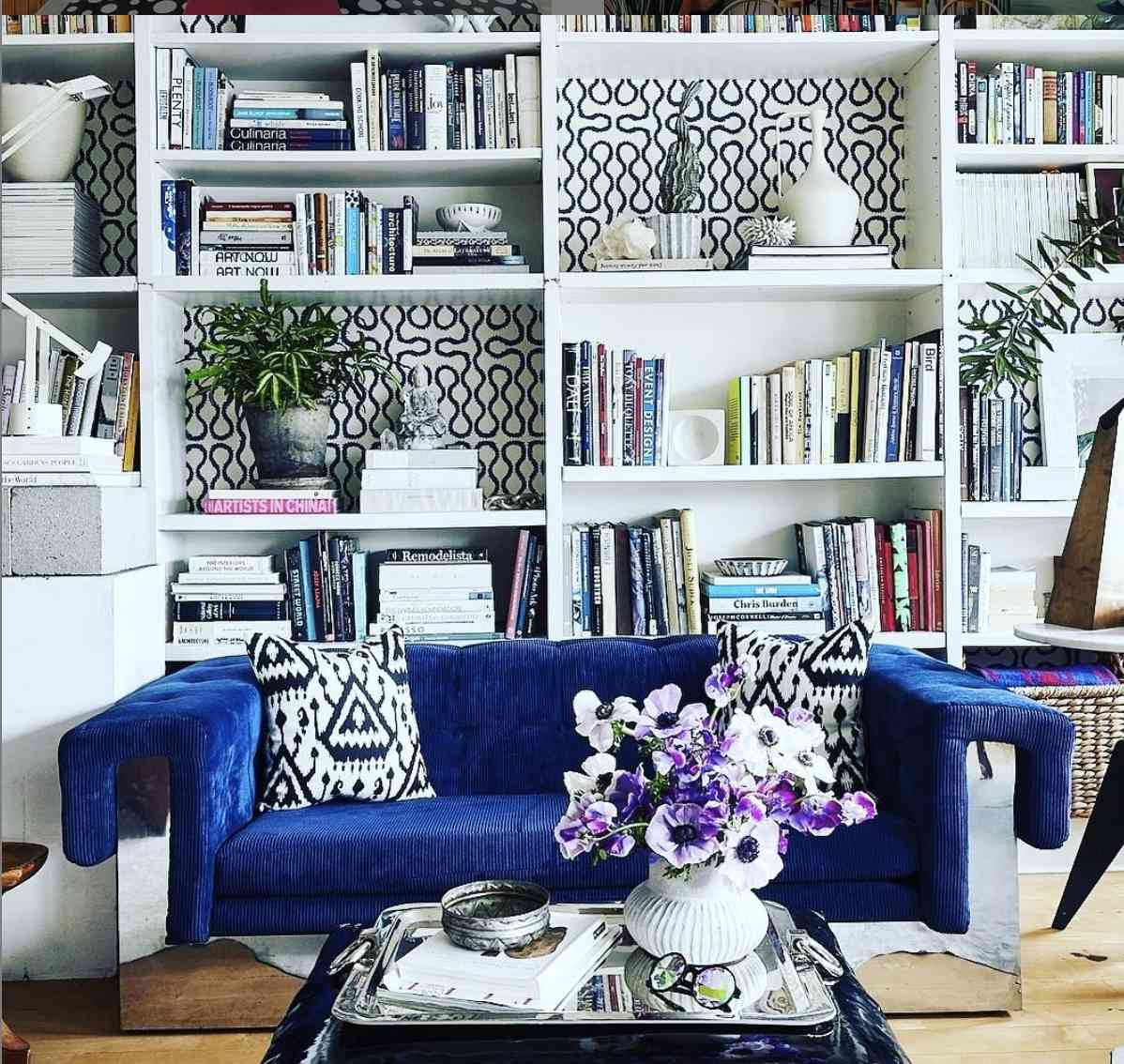 white bookshelves with wallpaper backing, blue couch