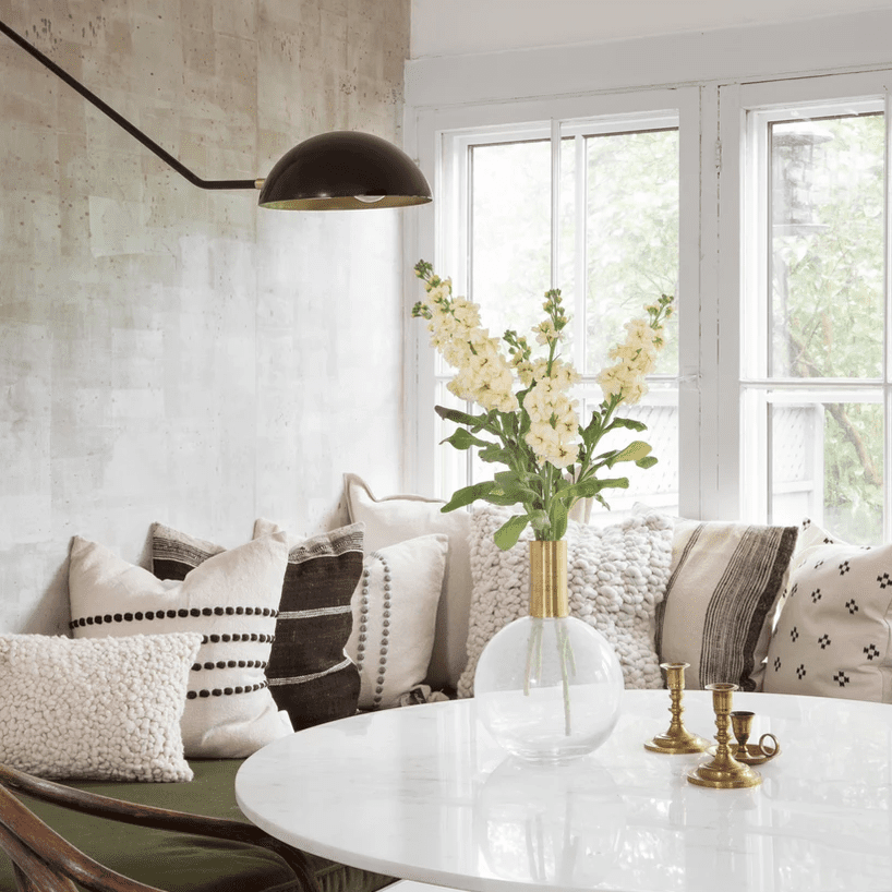 A dining nook with an array of ivory throw pillows