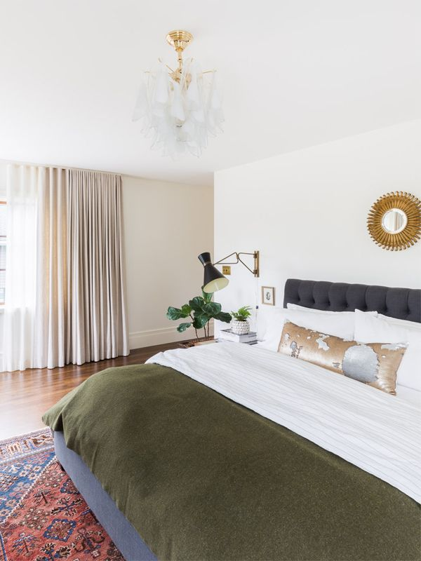 a neutral bedroom with decorative pillows and olive green bedding