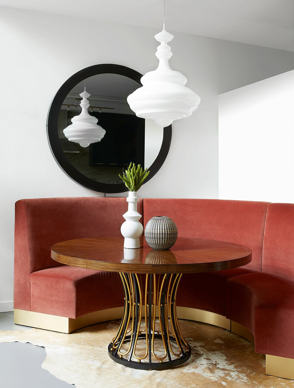 Breakfast nook features round pink booth, all-white hanging pendant light