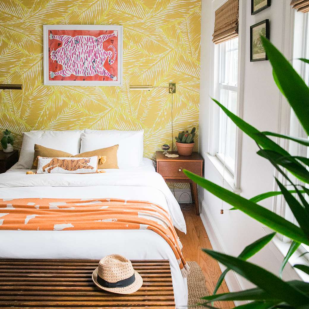 Bedroom with yellow wallpaper accent wall