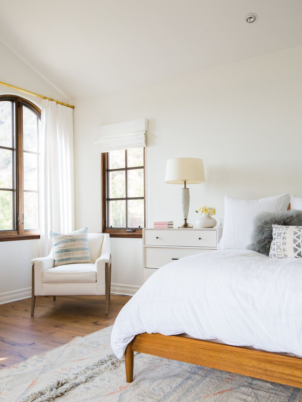 A bedroom with custom window treatments on windows of different shapes and sizes