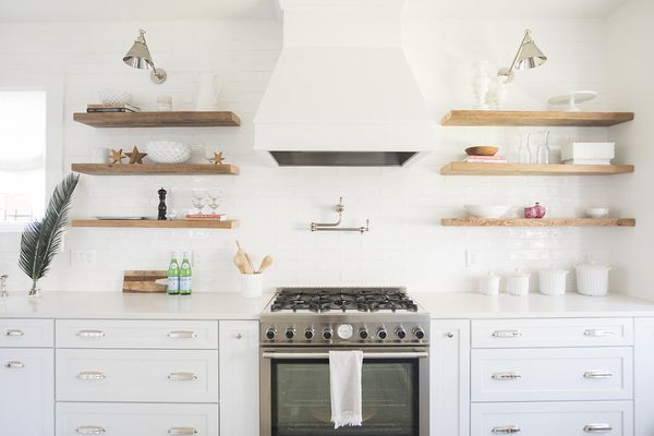 White kitchen with wooden open shelving.