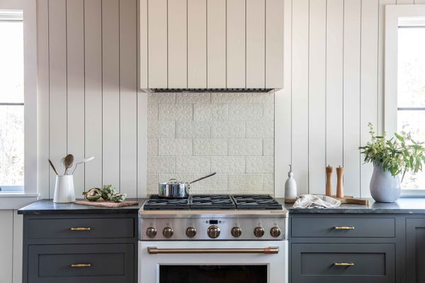 A kitchen with an ivory backsplash and a gas stove