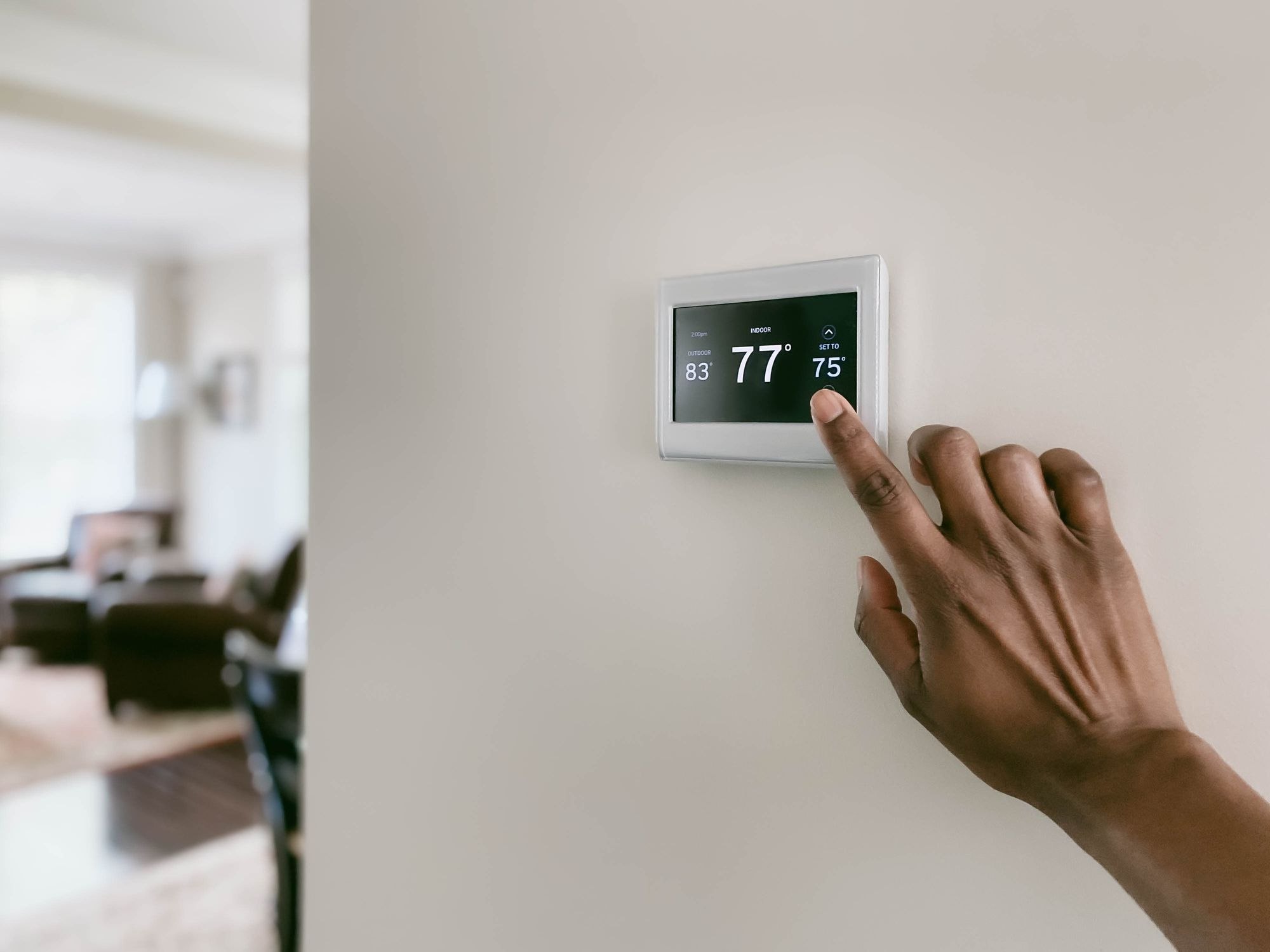Hand adjusts thermostat in living room