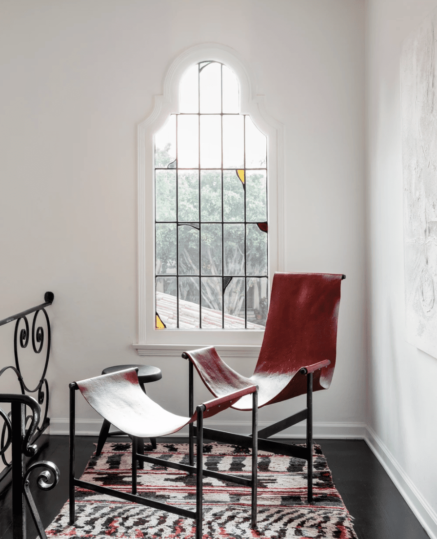 A corner of a home with a stained glass mirror and a red leather lounge chair