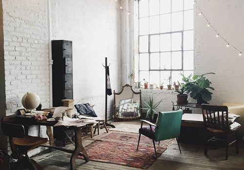 Open concept apartment with string lights and vintage furniture.