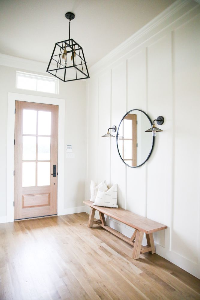 Minimalistic entryway with bench and large mirror