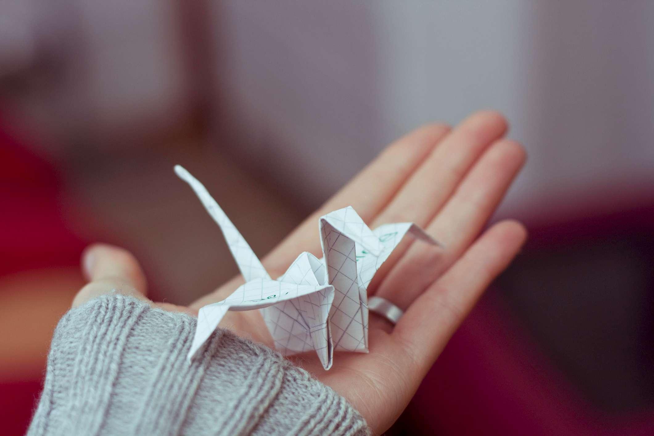 Paper crane on open palm