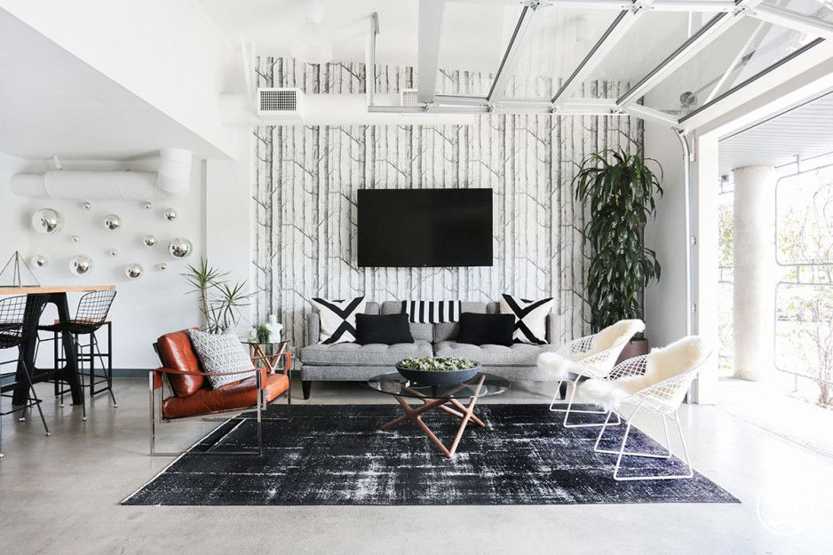 White living room with wallpapered accent wall.