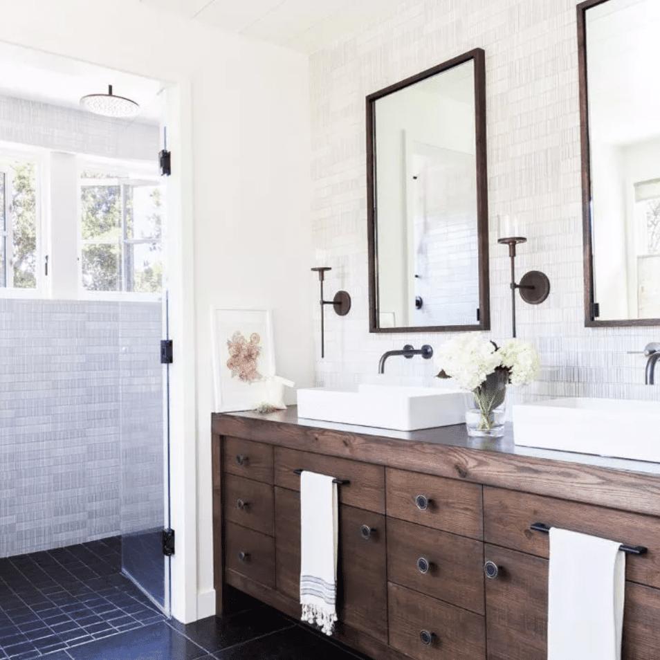 Tiled bathroom with white-tiled shower and black-tiled flooring