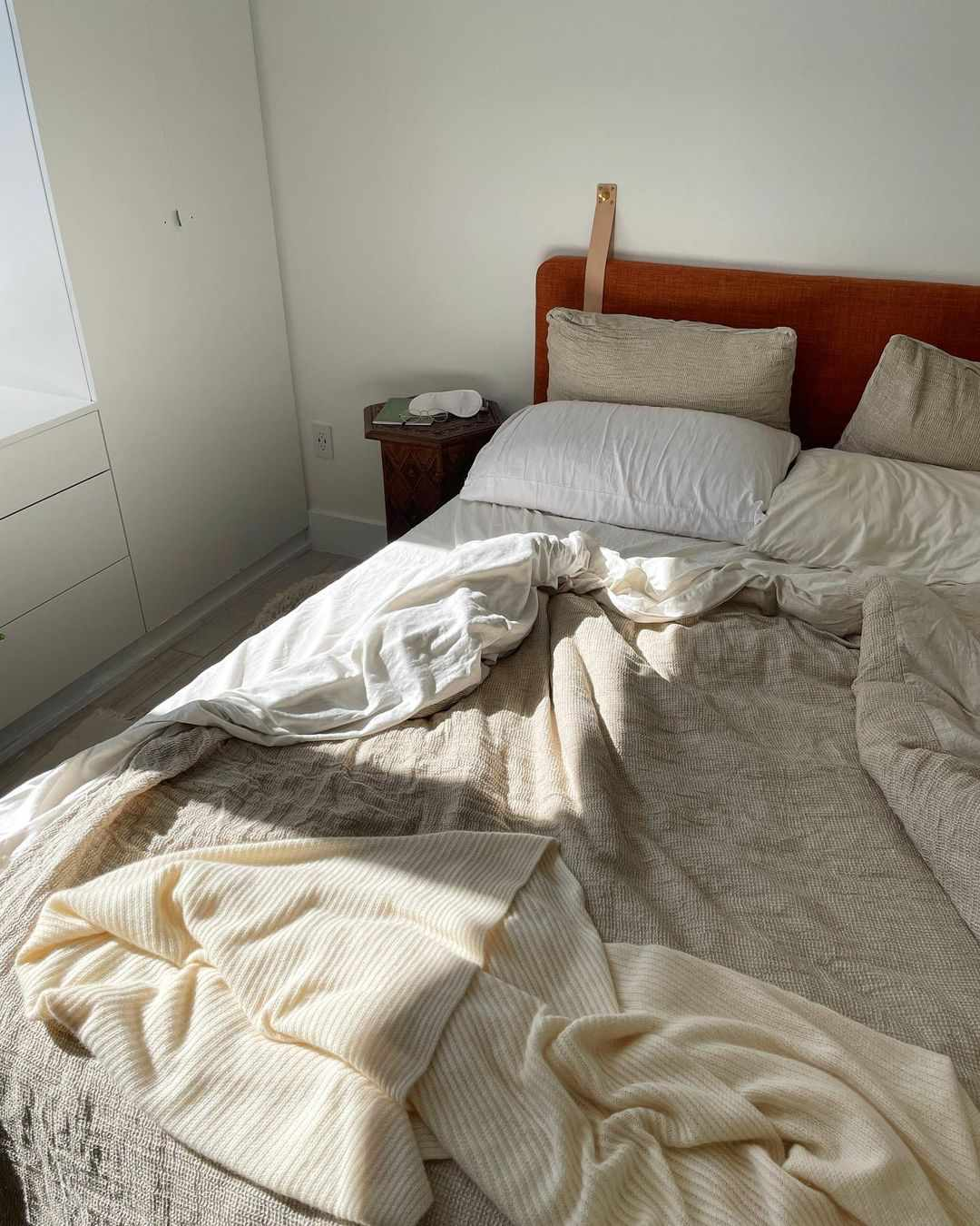 Messy bed with white and brown sheets.