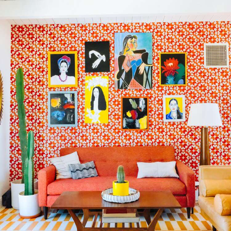 A maximalist room with red and orange printed wallpaper and a yellow printed rug
