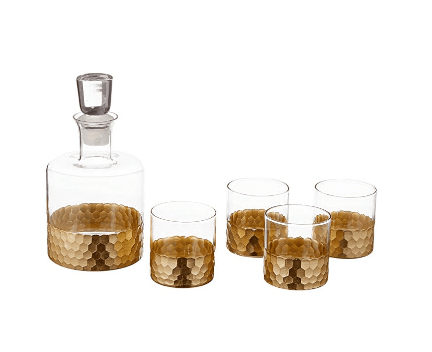 Set of four glasses with gold tone beehive pattern on their bottom halves, along with a matching crystal decanter.